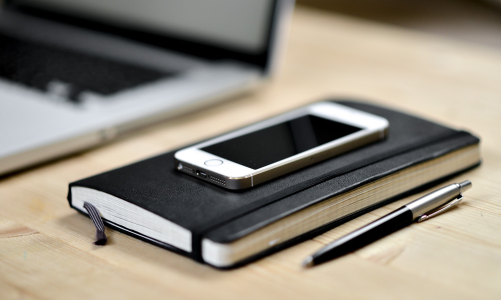 Smart-Phone-Notebook-Pen-and-Open-Laptop-On-Desk